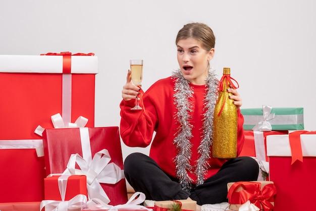 크리스마스 주위에 앉아 예쁜 여성 화이트 샴페인 축하 선물