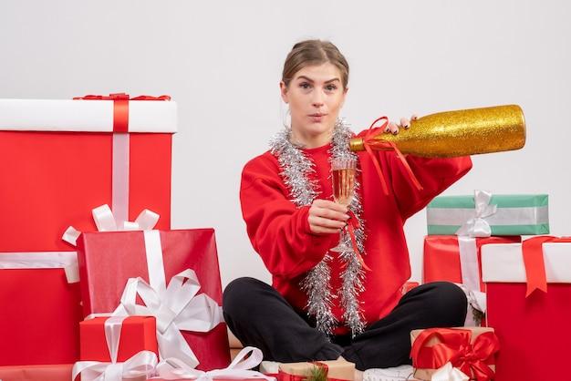 Bella donna seduta intorno a regali di natale che celebrano con champagne su bianco
