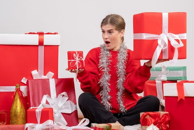 크리스마스 주위에 앉아 예쁜 여성 화이트 선물