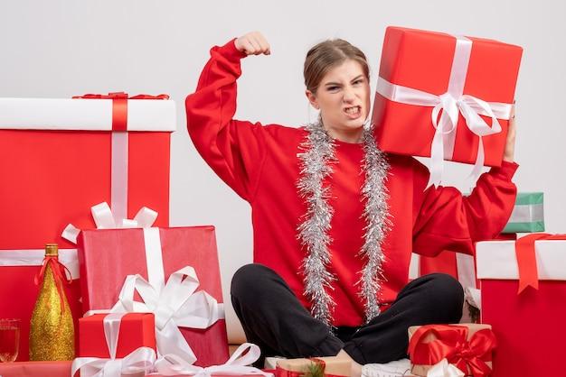 Bella donna seduta intorno a regali di natale su bianco