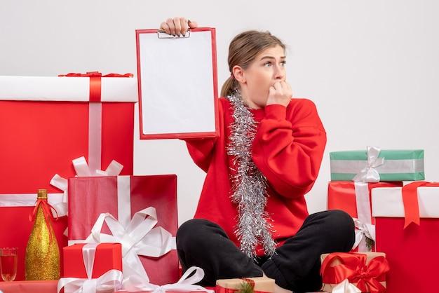 Bella donna seduta intorno a regali di natale con nota su bianco