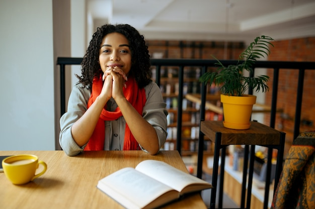 Pretty female student poses at the table with book in cafe
