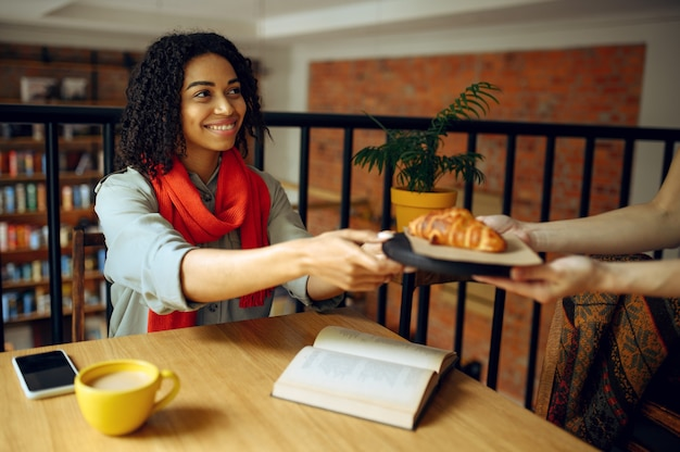 Pretty female student takes croissants in cafe