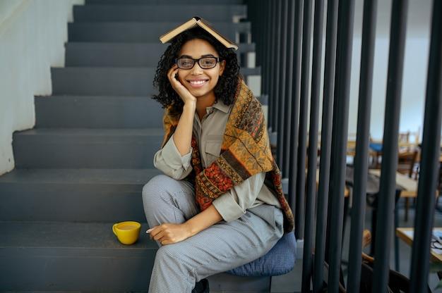 Довольно студентка с книгой, сидя на ступеньках в кафе библиотеки. женщина изучает предмет, образование и знания. девушка учится в кампусе