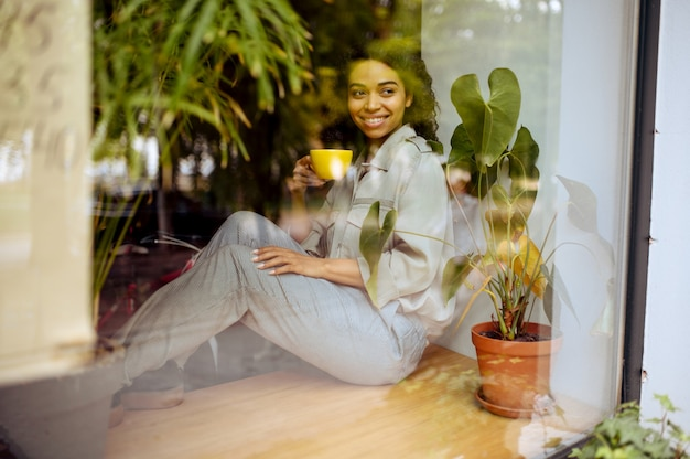 Pretty female student with cup of coffee sitting on the windowsill in cafe