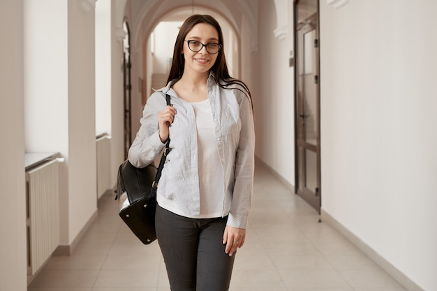 Pretty female student with long hair wearing eyeglasses posing with backpack on empty corridor of university. stylish woman going to lecture, smiling at camera. concept of study.