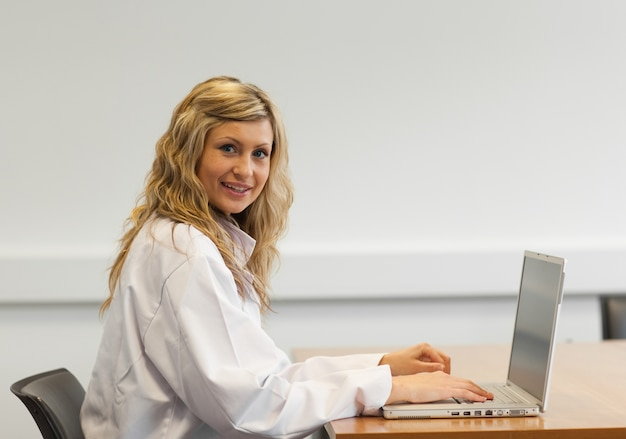 Pretty female surgeon working on a laptop