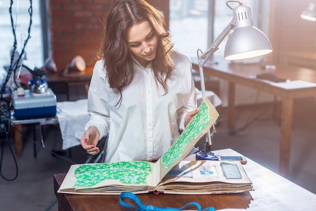 Симпатичная портная выбирает ткань в каталоге тканей
