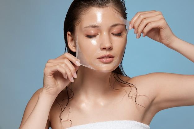 Красивая женщина снимает очищающую маску с закрытыми глазами