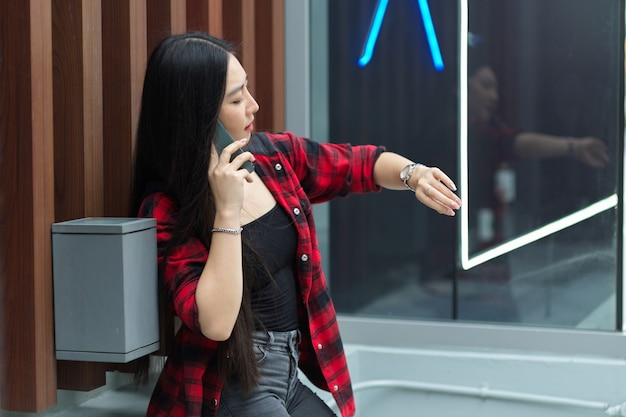 彼女の友人を待っている壁に寄りかかって彼女の腕時計を見ている電話で話しているきれいな女性