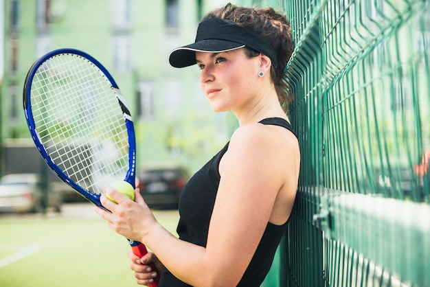 Pretty female tennis player holding a racket outdoors