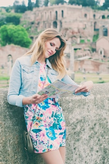 Довольно женщина турист, глядя на карту на руинах римского форума в риме, италия