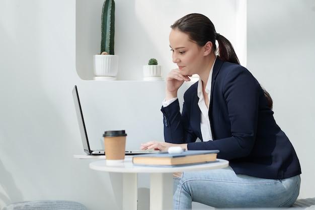 Довольно студентка университета работает на ноутбуке в кафе, пишет статью или эссе