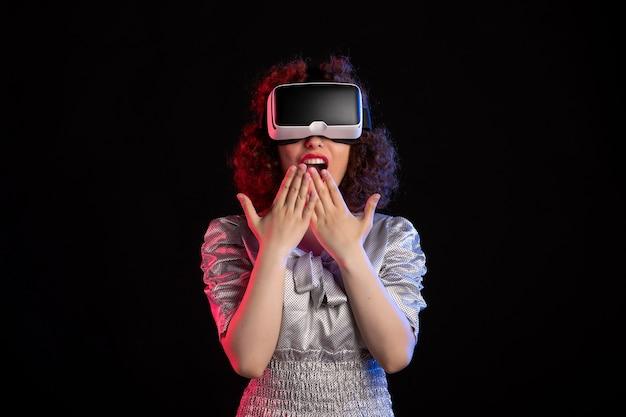 Pretty female wearing virtual reality headset on dark surface