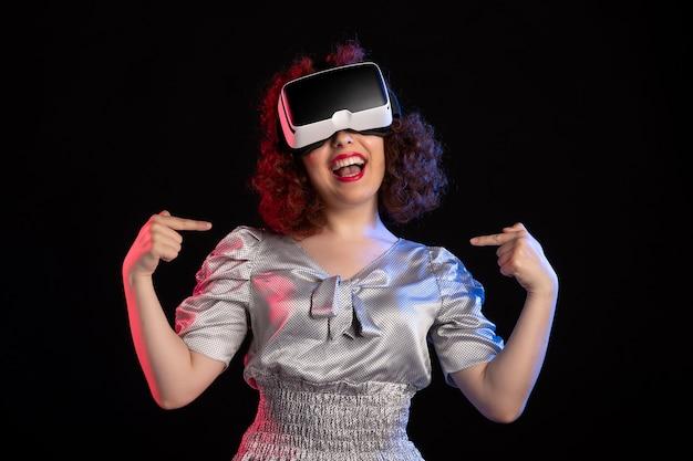 어두운 표면에 가상 현실 헤드셋을 착용하는 예쁜 여성
