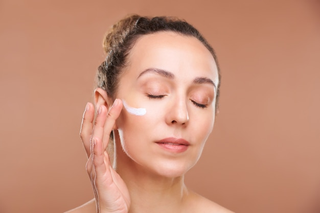 Pretty female with closed eyes applying cream on undereye area of her face while taking care of skin after morning hygiene in isolation