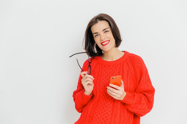 Pretty female with dark short hair, wears oversized red winter sweater, holds eyewear and smart phone