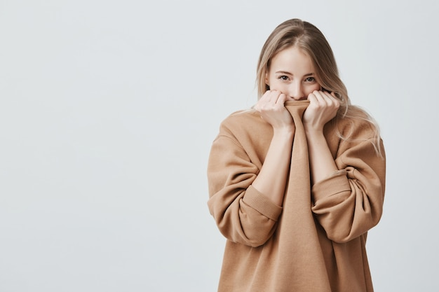 Pretty female with fair straight hair and dark appealing eyes hiding her face in warm loose sweater.