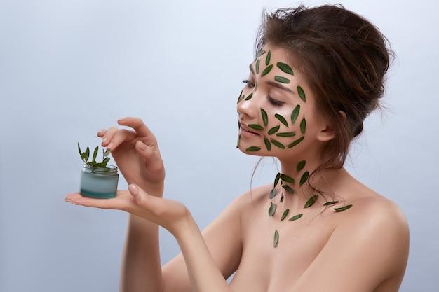 그녀의 팔에 천연 크림을 가진 몸에 녹색 잎을 가진 예쁜 여성