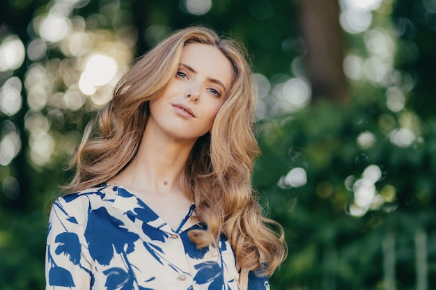 Pretty female with wavy hair, has blue eyes, dressed in elegant blouse, poses on nature