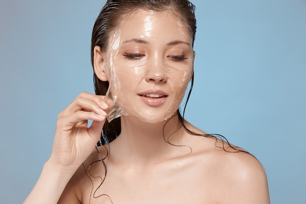Pretty female with wet hair taking off purifying transparent mask from face