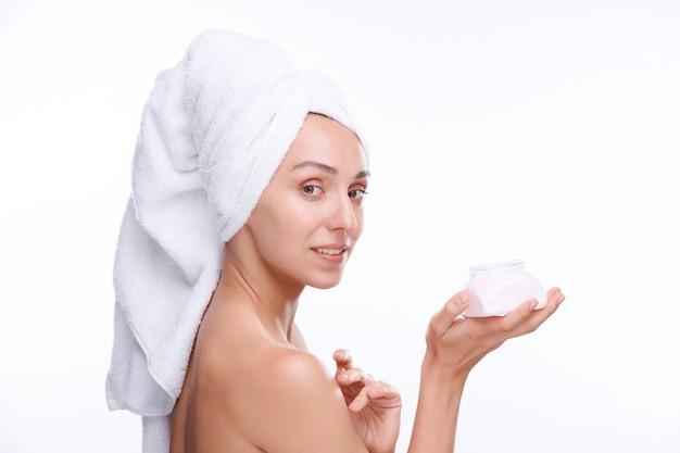 그녀의 어깨에 적용하는 동안 바디 크림을 부드럽게 플라스틱 항아리를 들고 머리에 흰색 부드러운 수건으로 예쁜 여성