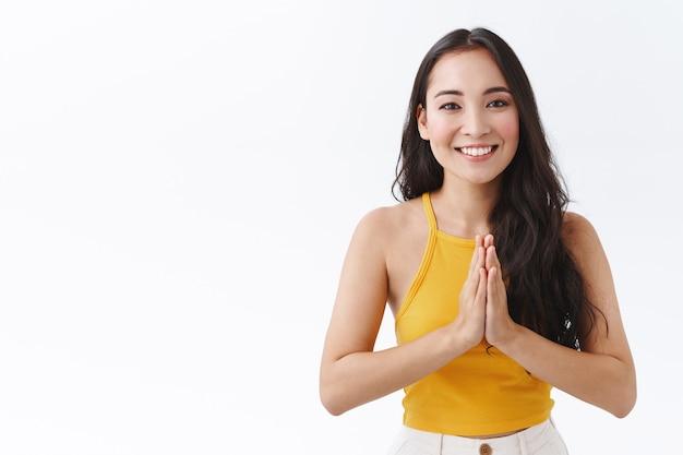 Довольно женственная восточноазиатская брюнетка в модном желтом топе, сцепив руки вместе в намасте, жестом мольбы или молитвы, беззаботно улыбается, смотрит с благодарностью, благодарит за помощь, белый фон