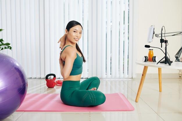 그녀의 블로그에 피트니스 비디오를 녹화할 때 소 얼굴 포즈를 하는 등 뒤에서 손을 꼭 잡고 있는 예쁜 아시아 여성