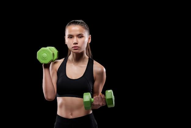 Симпатичная девушка в черной спортивной одежде держит зеленые гантели во время тренировки в тренажерном зале или спортивном центре с copyspace слева от нее
