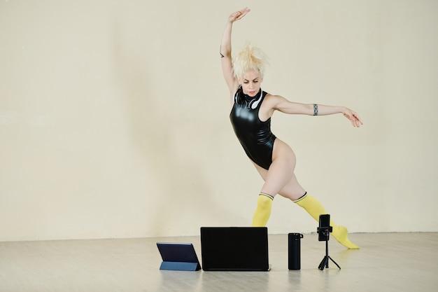 블로그나 교육용 비디오를 위해 춤을 추는 자신을 촬영하는 꽤 맞는 근육질의 여성