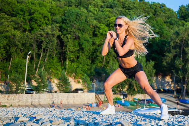 晴れた夏の日にかなりフィットする細身の女性の屋外フィットネス。屋外でエクササイズをする、健康的なアクティブライフスタイルのコンセプト。ジャンプスクワット。うれしい