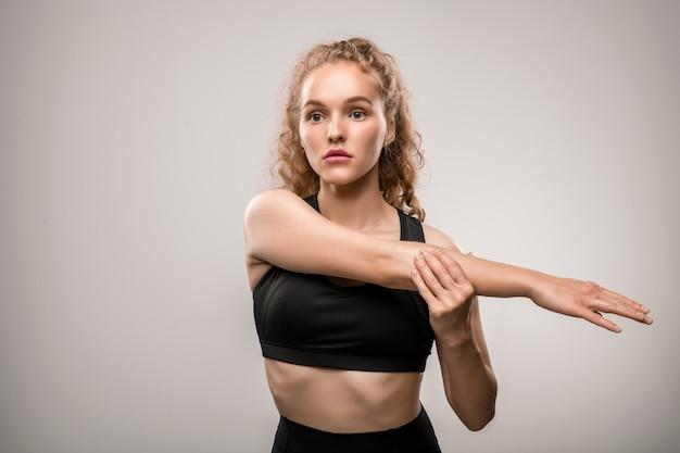 Симпатичная спортсменка в черном спортивном костюме протягивает правую руку перед собой во время тренировки на сером в тренажерном зале