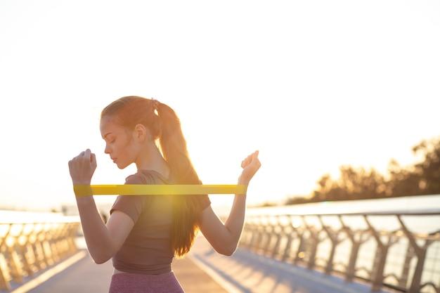 朝の橋で輪ゴムでエクササイズをしているスポーツアパレルに身を包んだ赤い髪のかなりフィットした女性。テキスト用のスペース