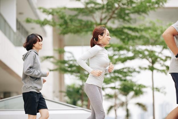 Довольно подтянутая молодая азиатская женщина в удобной спортивной одежде бегает трусцой на открытом воздухе с группой друзей