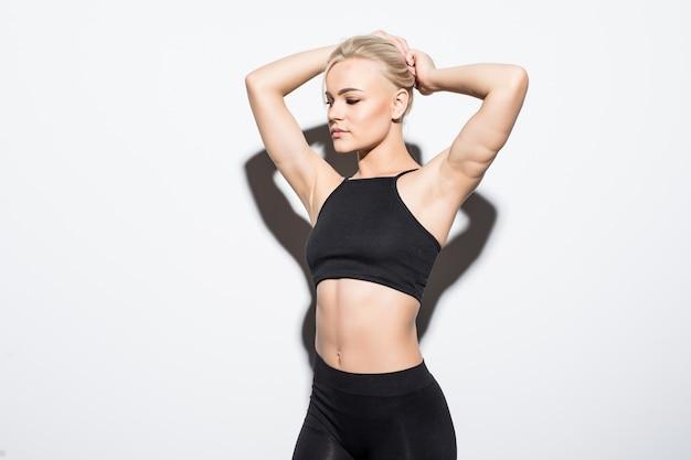 Девушка довольно фитнеса устала и чувствует себя утомленной в студии на белом, одетая в черную спортивную одежду