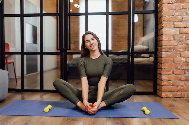 Pretty fitness model doing strenghth with yellow dumbbells on a mat at home