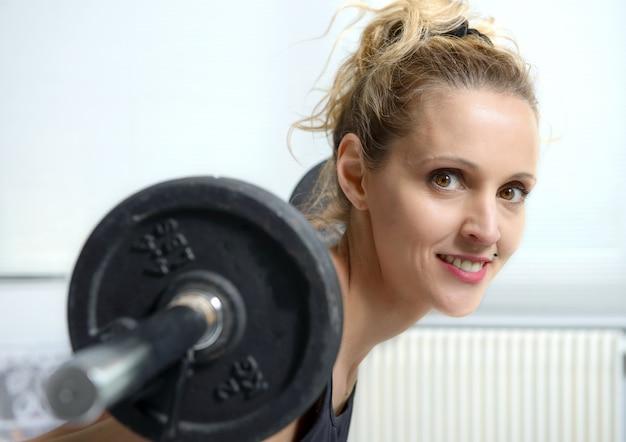 Pretty fitness woman lifting dumbbells
