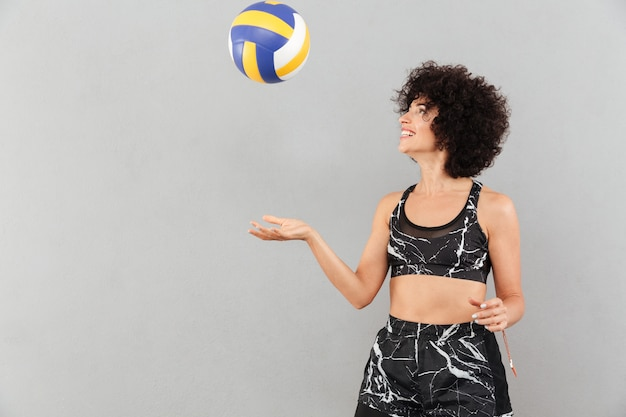 Pretty fitness woman playing with ball