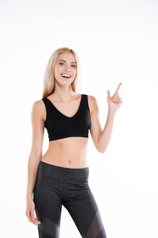 Pretty fitness woman pointing to copyspace