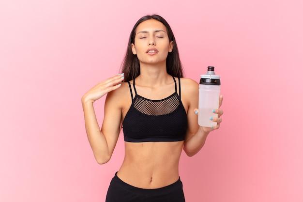 水のボトルを持つかなりフィットネスの女性
