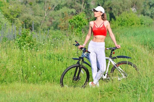 Женщина довольно фитнес с велосипедом на открытом воздухе