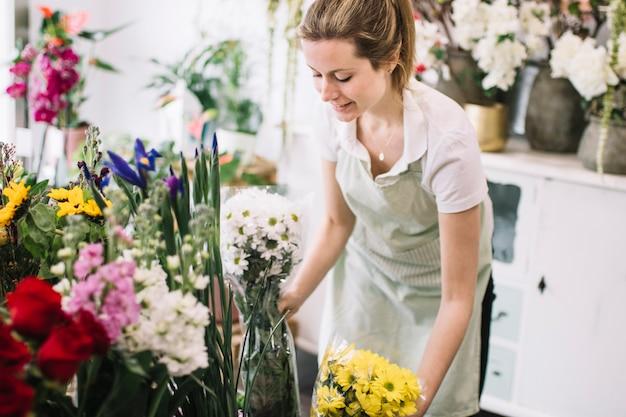 Довольно флорист организует букеты в магазине