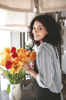 色とりどりの花の美しい花束を作成するエプロンのかわいい花屋。チューリップと立っている暗い巻き毛の若いアフリカ系アメリカ人の女の子