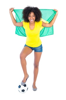 Pretty football fan holding brazilian flag cheering at camera