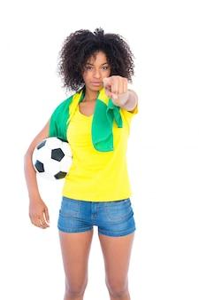 Pretty football fan holding brazilian flag pointing at camera