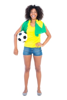 Pretty football fan holding brazilian flag smiling at camera