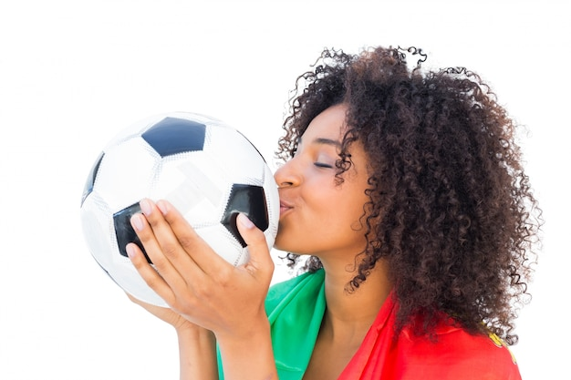 Pretty football fan with portugal flag kissing ball