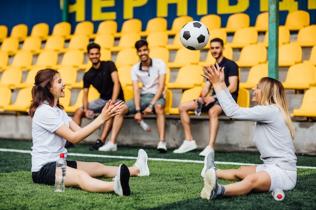 Uomo grazioso del giocatore di football che allunga il muscolo della gamba che si prepara per la partita nello stadio