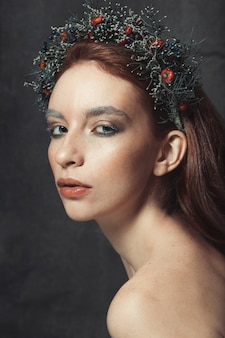 かなりそばかすのある少女を裸の肩と彼女の頭に花輪を捧げる肖像画を閉じる Premium写真
