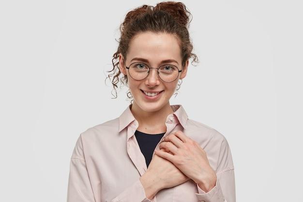 白い壁に向かってポーズをとっている眼鏡をかけたかなりそばかすのティーンエイジャー